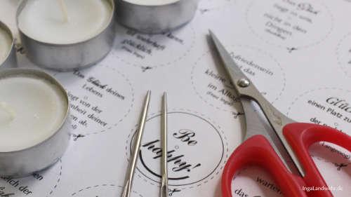 Teelichter, 2 Wollnadeln, kleine Schere liegen auf einem Ausdruck mit Glückszitaten