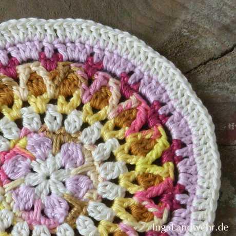 Ein gehäkeltes Agni-Mandala in Rosa- und Gelbtönen
