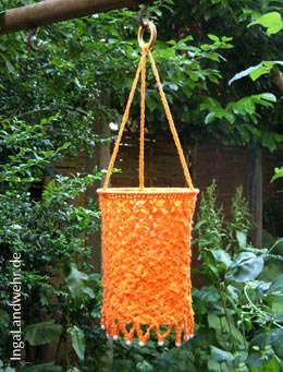 Gehäkelte Gartenlaterne hängt im Garten