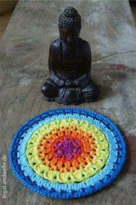 Ein Holzbuddha meditiert vor einem Mandala in Regenbogenfarben