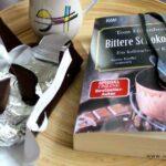 Das Buch Bittere Schokolade liegt mit einer aufgerissenen Schokoladentafel auf einem Tablett