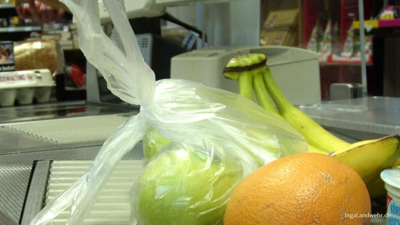 Gemüse in Plastiktüten liegt auf dem Laufband an der Kasse in einem Supermarkt auf Langeoog