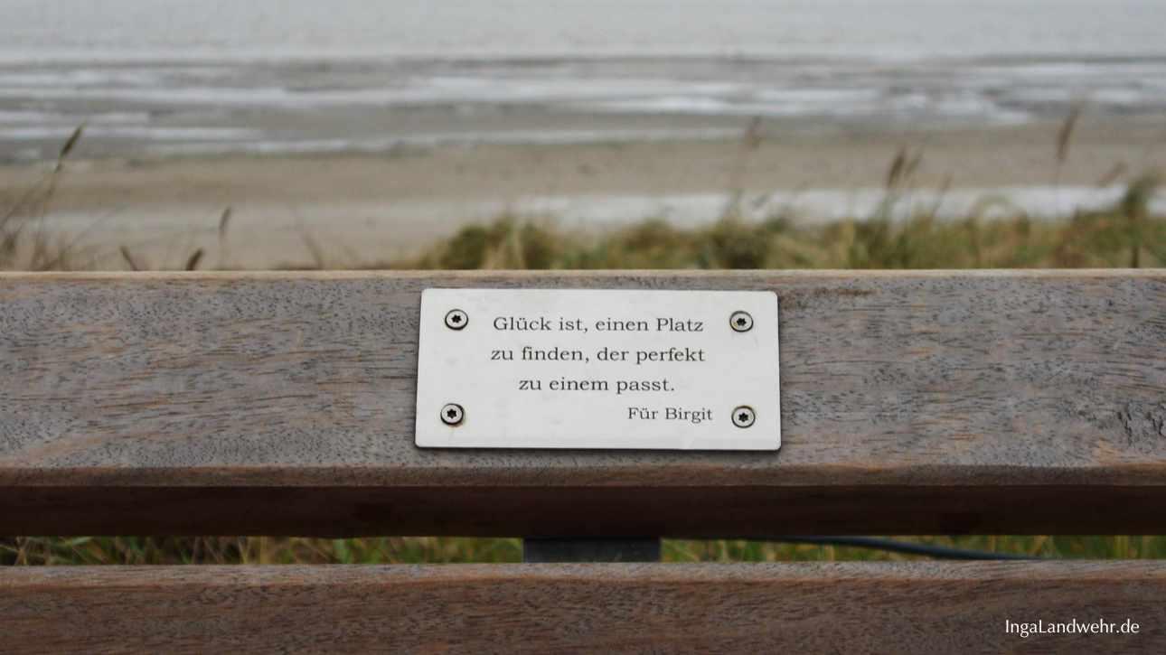 """Plakette auf einer Bank mit der Gravier: """"Glück ist, einen Platz zu finden, der perfekt zu einem passt."""" Im Hintergrund ist die Nordsee"""