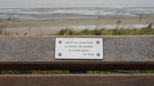 """Bank am Strand. Gravur auf einer Plakette: """"Glück ist, einen Platz zu finden, der perfekt zu einem passt."""""""