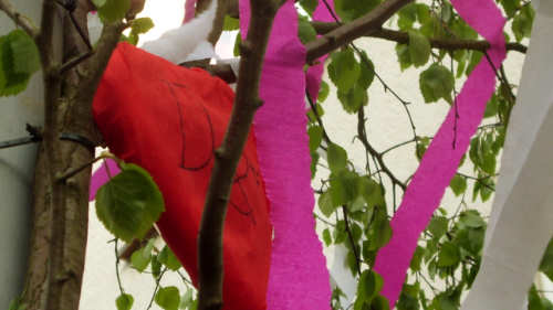 Ein rotes Herz aus Krepppapier im Maibaum