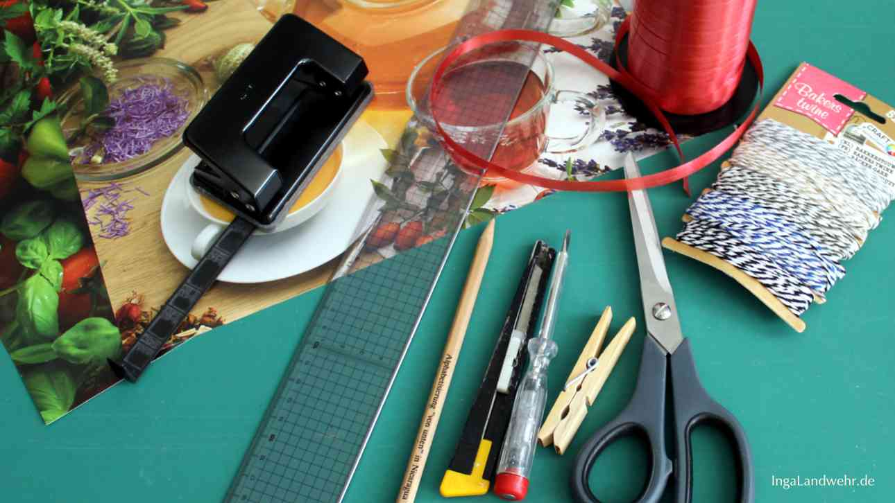 Schere, Bleistift, Cutter, Lineal, Locher, Schneidemappe und Kalenderblätter werden für selbstgebastelte Papiertüten gebraucht.