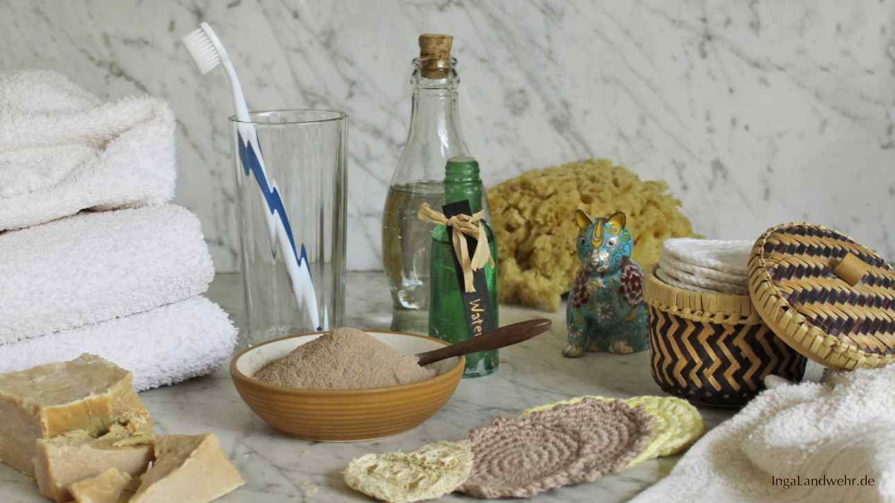 Diverse nachaltige Badezimmerutensilien: Seife, Rassoul, gehäkelte Kosmetikpads, Waschlappen und Handtücher