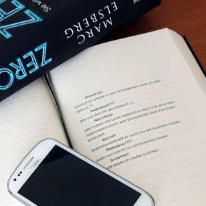 Zero, aufgeschlagen auf Seite 227, darauf ein Smartphone