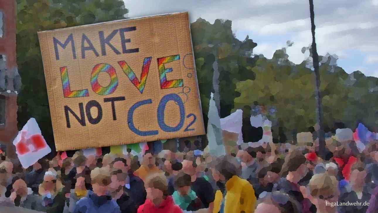"""Menschen, die für Nachhaltigkeit demonstrieren. Im Vordergrund ein Schild mit der Aufschrift """"Make Love not CO2"""""""