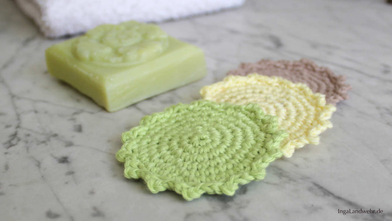 Drei gehäkelte Kosmetikpads in den Farben grün, gelb und mittelbraun.