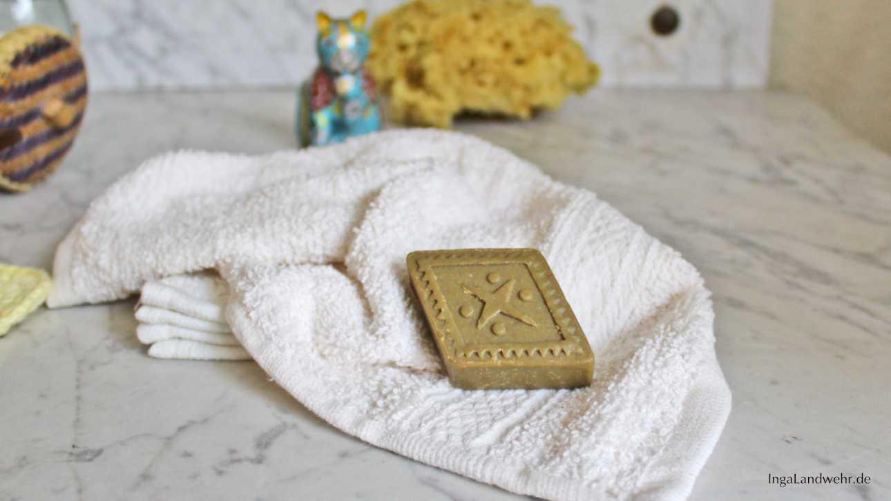 Ein Stück Seife liegt auf einem Waschlappen. Im Hintergrund ist ein Naturschwamm und eine Katzenfigur zu sehen.