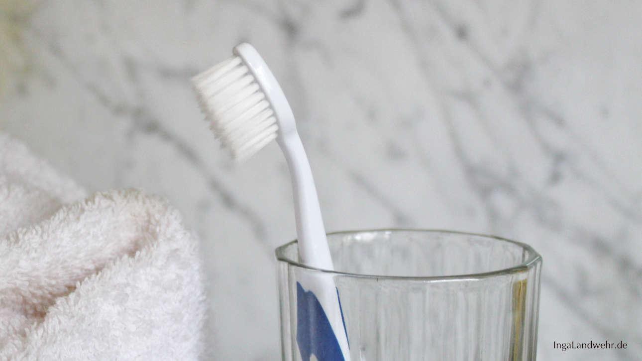 Eine Zahnbürste steckt in einem Wasserglas