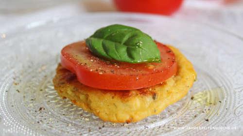 Hüttenkäsepuffer mit einer Tomatenscheibe und einem Basilikumblatt darauf.
