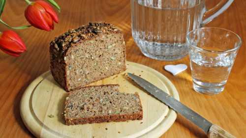 Brot auf einem Holzbrett und ein Glas Wasser daneben als Fastenspeise