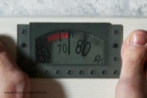 Der Zeiger einer Personen zeigt 74 kg an. Der Skalenbereich von 64 - 74 kg ist rot markiert.