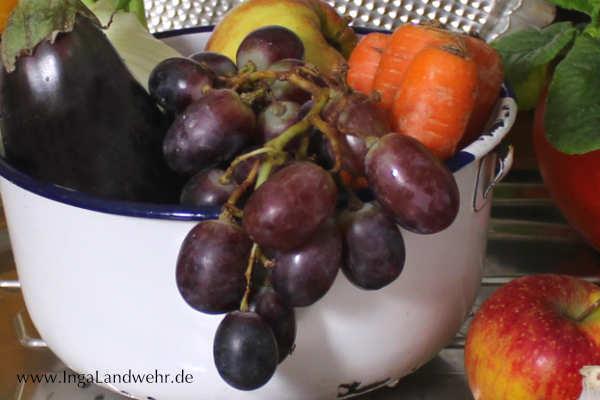 Rote Wentrauben liegen mit Äpfeln und Karotten in einer weißen Schüssel