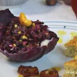 Rotkohlsalat ist in einem Rotkohlblatt angerichtet. Darauf liegt ein Cashewkern und daneben zwei Hüttenkäse-Küchlein