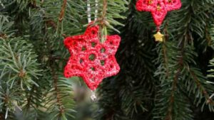 Zwei rote Häkelsterne hängen in einem Weihnachtsbaum