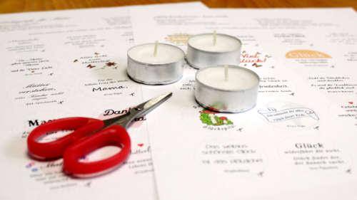 Vierfarbige Vorlagen für Glücksteelichter. Darauf liegt eine Schere sowie drei Teelichter.