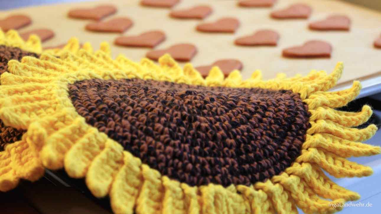 Auf einem Backblech mit Keksen liegen Sonnenblumen-Topflappen