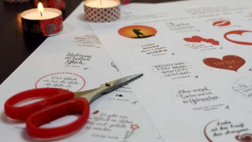 Vorlagen für Glücksteelichter mit Motiven für Glück und Liebe. Im Hintergrund brennen Teelichter.