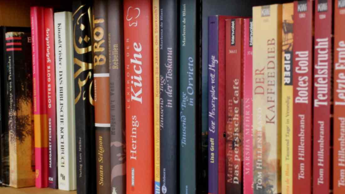 In einem Regal steht eine Reihe mit Kochbüchern