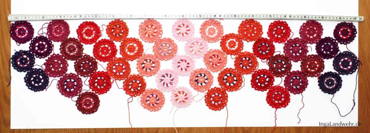 Viele Häkelblumen für die Bistrogardine sind nach Farben geordnet auf einem Tisch ausgelegt