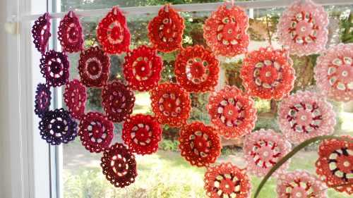 Vor einem Fenster hängt eine Scheibengardine aus viele Häkelblüten in Rottönen